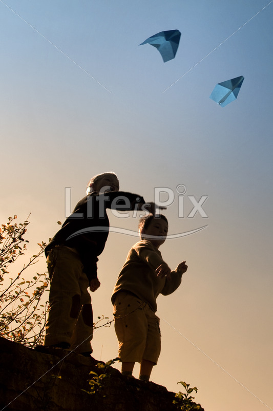 Two children playing with paper airplanes